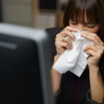 Woman sneezing into a tissue.